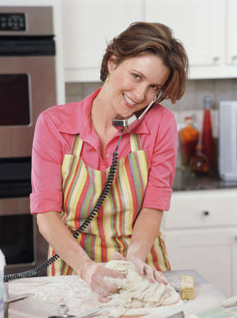 Young woman cooking and talking on the phone simultaneously