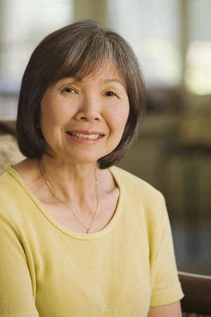 Senior Asian woman smiling indoors LANG_EVOIMAGES