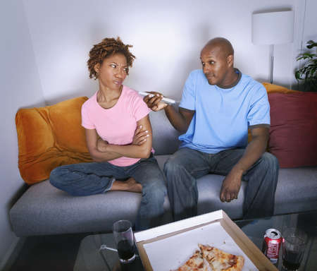 African man pointing remote control at annoyed girlfriend LANG_EVOIMAGES