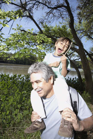 Hispanic grandfather holding grandson on his shoulders outdoors LANG_EVOIMAGES