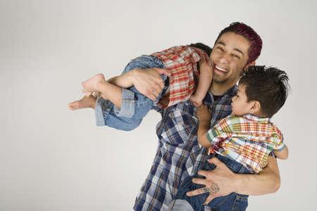 Hispanic father holding toddler children LANG_EVOIMAGES