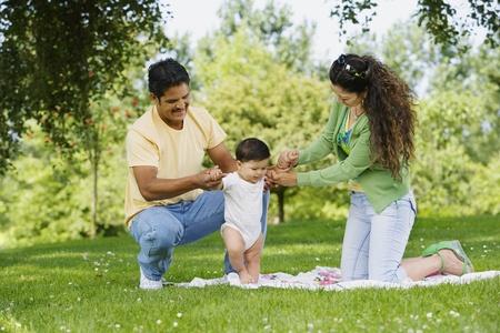 Hispanic parents helping baby walk in park