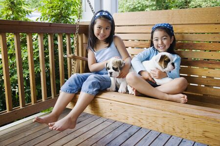 Young Asian sisters sitting on porch swing with puppies