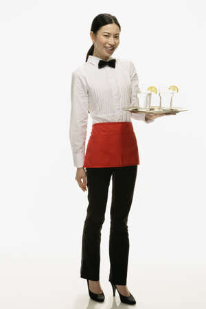 Studio shot of Asian waitress holding tray of drinks LANG_EVOIMAGES