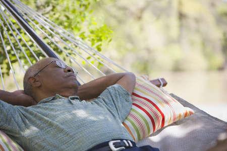 Senior African man laying in hammock LANG_EVOIMAGES