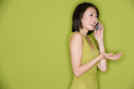 Studio shot of Asian woman using cell phone