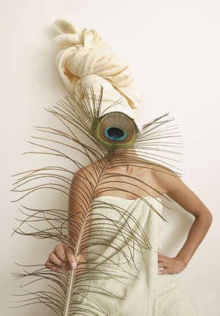 Woman in towel holding peacock feather
