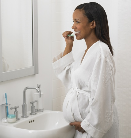 Pregnant African woman brushing teeth