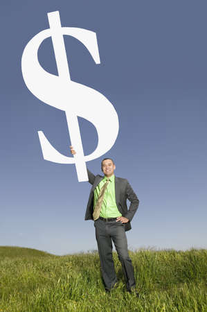 Asian businessman holding dollar sign in field