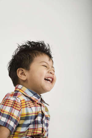 Studio shot of young Hispanic boy laughing