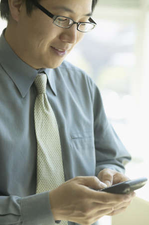 Asian businessman typing on cell phone