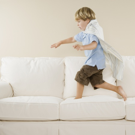 Young boy playing on sofa LANG_EVOIMAGES