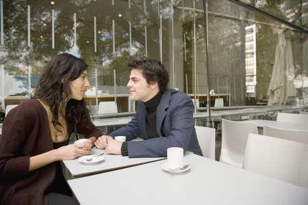 Hispanic couple talking at cafe