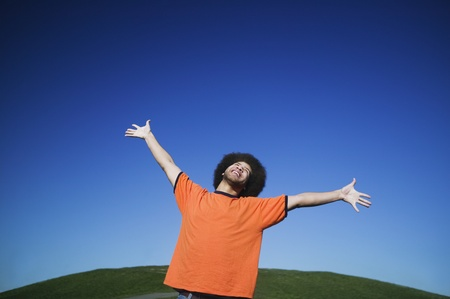 African man with arms raised under blue sky LANG_EVOIMAGES