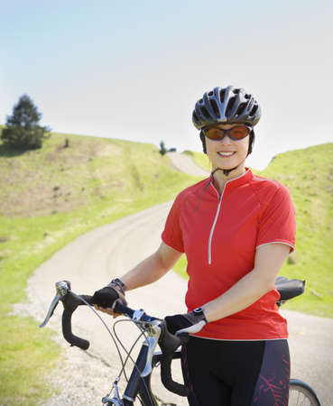 Asian woman wearing bicycle gear with bicycle LANG_EVOIMAGES