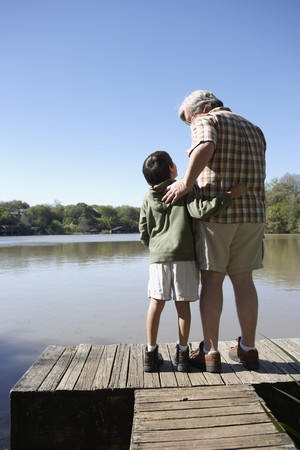 Grandfather and grandson standing on wooden dock