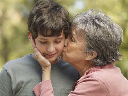 Hispanic grandmother kissing grandson on cheek LANG_EVOIMAGES