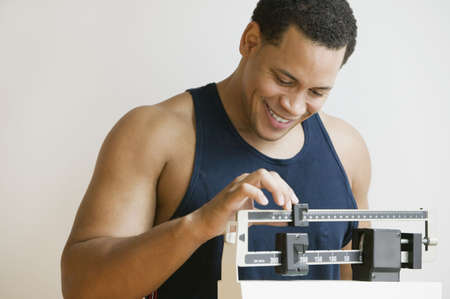 African American man weighing himself on scale LANG_EVOIMAGES