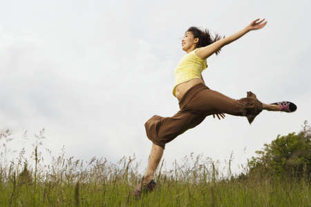 Asian woman jumping in meadow