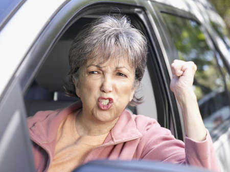 Angry senior Hispanic woman in driverís seat of car LANG_EVOIMAGES