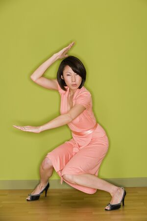 Asian woman in dress doing martial arts move