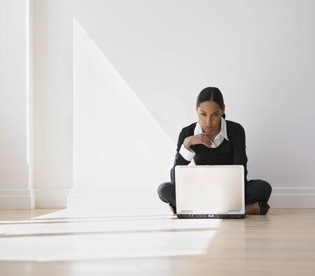 African businesswoman on floor looking at laptop