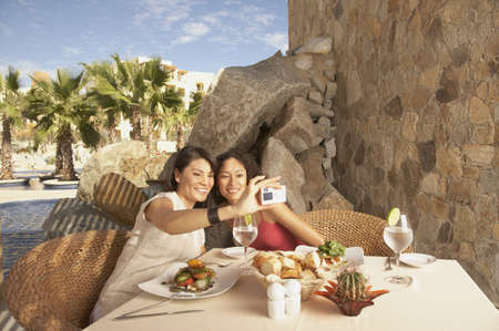 Two women taking a photograph of themselves at a resort hotel, Los Cabos, Mexico LANG_EVOIMAGES