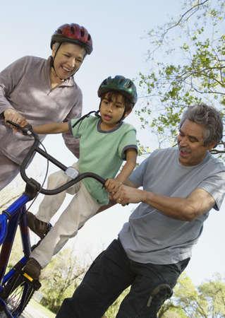 Hispanic grandparents helping grandson ride bicycle LANG_EVOIMAGES