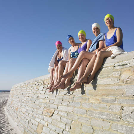 Group of senior women in bathing suits sitting on stone wall at beach
