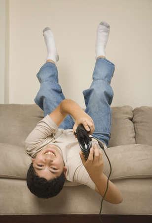 Hispanic boy playing video games upside down on sofa