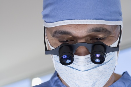 Close up of African male doctor with surgical mask and binocular loupes
