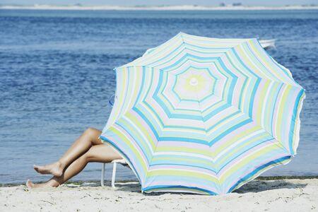 Woman sitting under beach umbrella LANG_EVOIMAGES