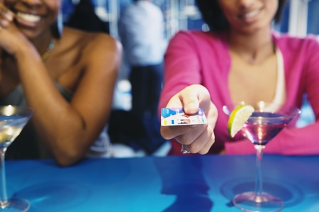 African woman handing credit card over bar LANG_EVOIMAGES