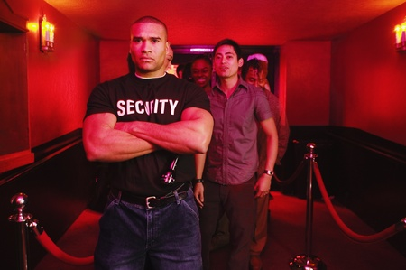 African male bouncer with arms crossed in front of people