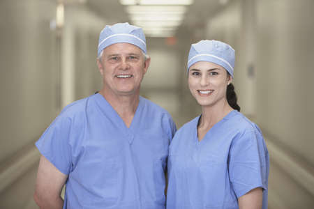Male and female doctor in hospital corridor