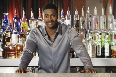 African male bartender leaning on bar