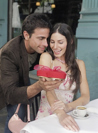 Hispanic man giving girlfriend gift at cafe