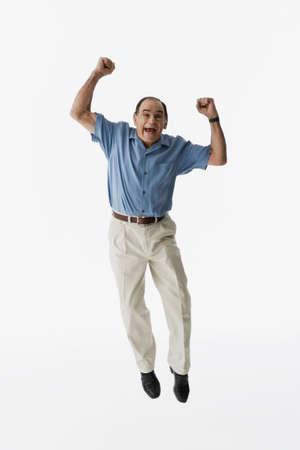 Senior Hispanic man jumping LANG_EVOIMAGES