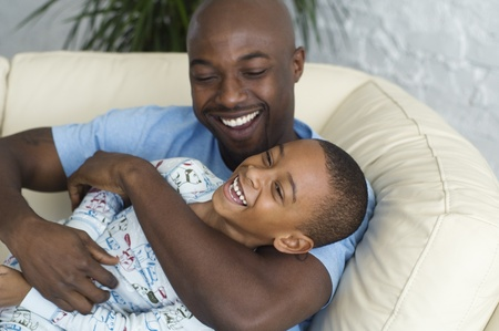 African father tickling son