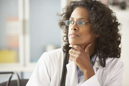 African female doctor looking to side with chin in hand
