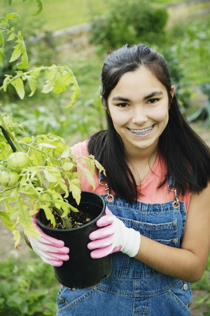 Girl holding tomato plant