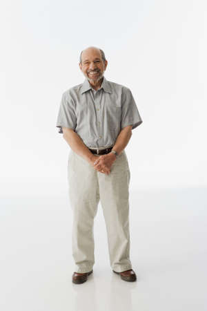 Senior man standing with hands clasped LANG_EVOIMAGES