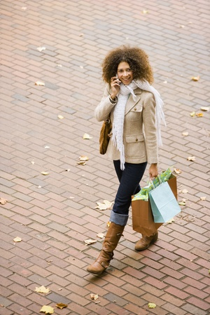 Hispanic woman walking with cell phone and shopping bags