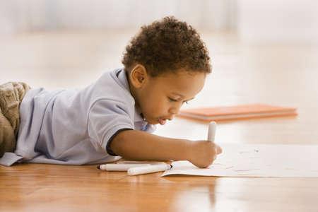 African boy coloring on floor