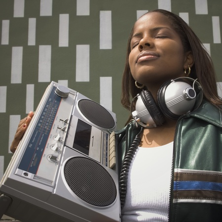 Low angle view of African woman listening to music on portable stereo LANG_EVOIMAGES