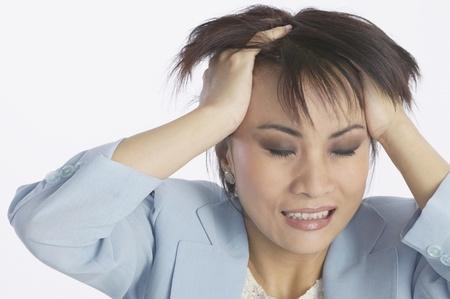 Asiatische Geschäftsfrau mit den Händen im Haar LANG_EVOIMAGES