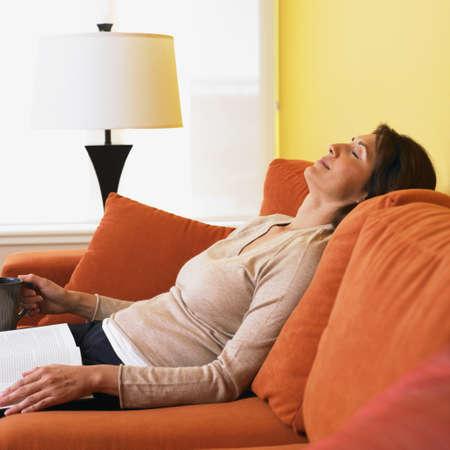 Hispanic woman resting on sofa