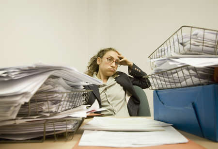 Hispanic businesswoman looking at piles of paperwork