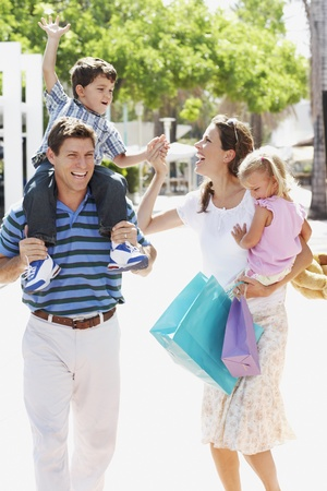 Hispanic family walking with shopping bags outdoors