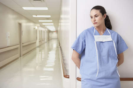 Female doctor leaning against wall in hospital corridor